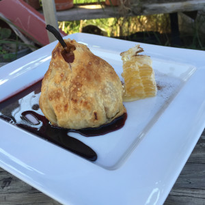 Pear poached in red wine stuffed with Drake farm apricot goat cheese wrapped in pastry served with red wine syrup and chai dusted honeycomb